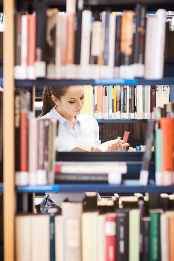 Νέος σπουδαστής που ψάχνει για τα βιβλία στοκ εικόνες