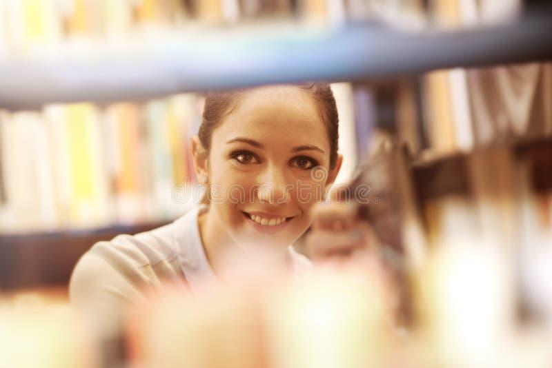 Νέος σπουδαστής που ψάχνει για τα βιβλία στοκ εικόνες με δικαίωμα ελεύθερης χρήσης