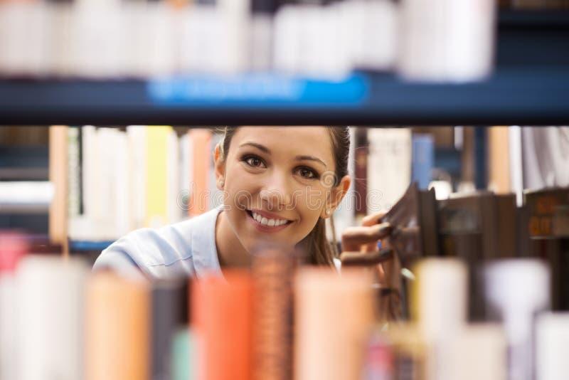 Νέος σπουδαστής που ψάχνει για τα βιβλία στοκ εικόνα με δικαίωμα ελεύθερης χρήσης