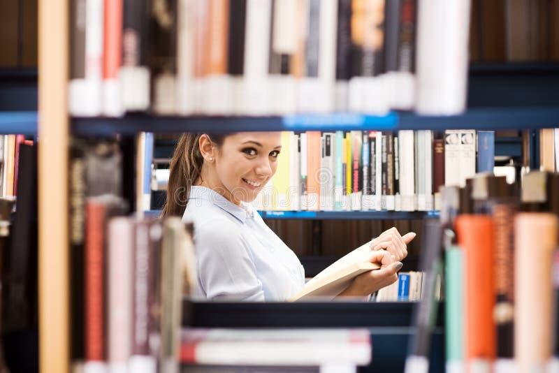 Νέος σπουδαστής που ψάχνει για τα βιβλία στοκ φωτογραφίες