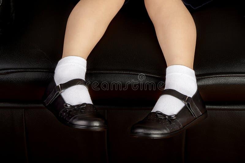 Νέος σπουδαστής σχολικών κοριτσιών που φορά τα μαύρα παπούτσια στοκ εικόνα