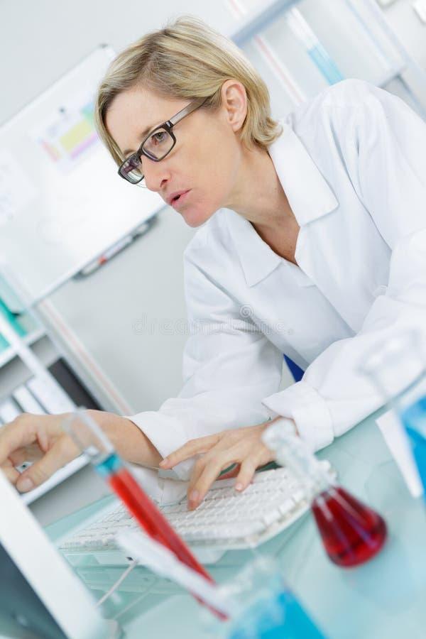 Νέος στοχαστικός θηλυκός φαρμακοποιός που εργάζεται στο εργαστήριο στοκ εικόνες