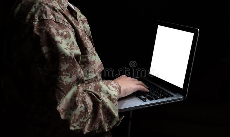 Νέος στρατιώτης που εργάζεται με έναν φορητό προσωπικό υπολογιστή με την κενή οθόνη στο μαύρο υπόβαθρο στοκ φωτογραφίες με δικαίωμα ελεύθερης χρήσης