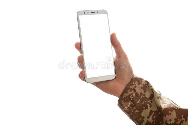 Νέος στρατιώτης που κρατά ένα κινητό τηλέφωνο με την κενή οθόνη στο άσπρο υπόβαθρο στοκ φωτογραφία με δικαίωμα ελεύθερης χρήσης
