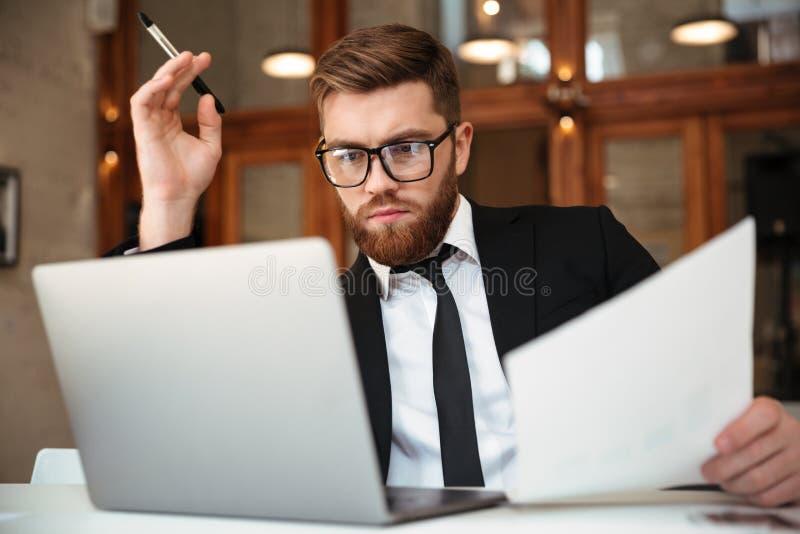 Νέος συγκεντρωμένος γενειοφόρος επιχειρηματίας στη formalwear εξέταση στοκ φωτογραφίες