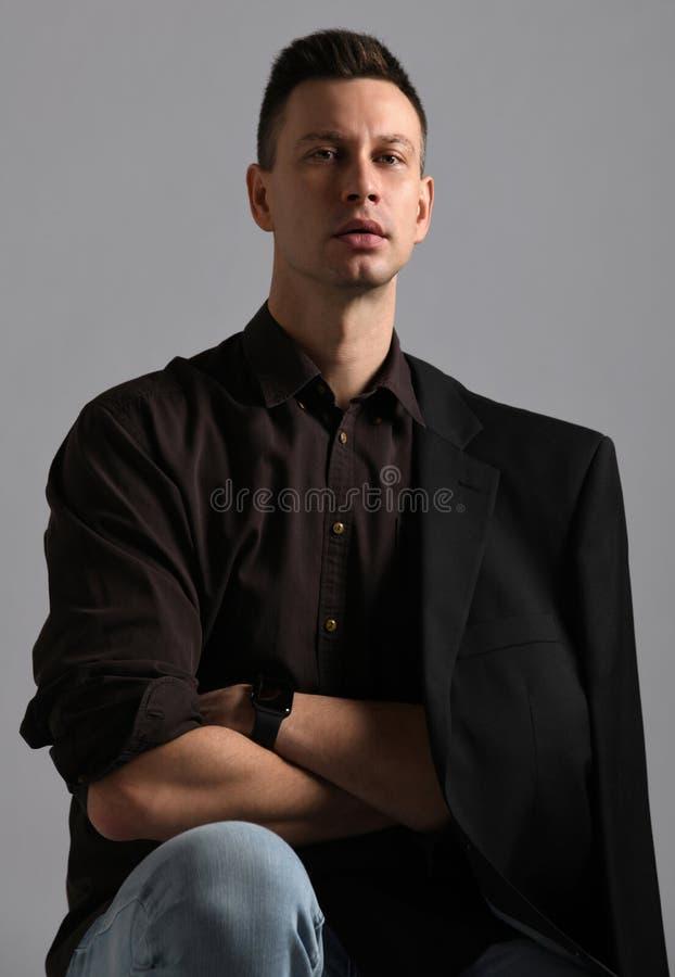 Νέος σύγχρονος επιχειρηματίας στο μαύρο πουκάμισο με το ρόλο επάνω στα μανίκια, το σακάκι και το τζιν παντελόνι στοκ εικόνα