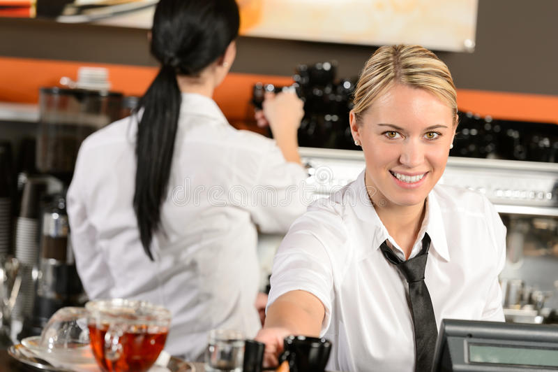 Νέος ταμίας σερβιτορών που δίνει τον καφέ στον καφέ στοκ εικόνες