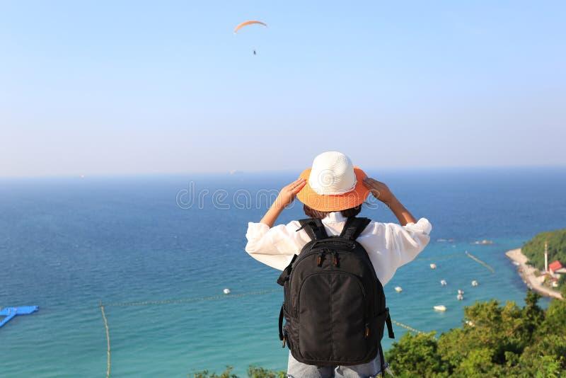 Νέος ταξιδιώτης γυναικών με το σακίδιο πλάτης που απολαμβάνει και που στέκεται στα βουνά του υποβάθρου θάλασσας, Koh Larn στην πό στοκ εικόνες