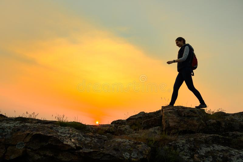 Νέος ταξιδιώτης γυναικών που με το σακίδιο πλάτης στο δύσκολο ίχνος στο θερμό θερινό ηλιοβασίλεμα Έννοια ταξιδιού και περιπέτειας στοκ φωτογραφία με δικαίωμα ελεύθερης χρήσης