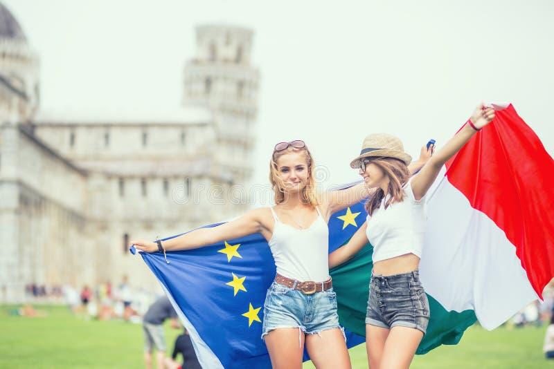 Νέος ταξιδιώτης κοριτσιών εφήβων με τις σημαίες ιταλικών και ευρωπαϊκών ενώσεων πριν από τον ιστορικό πύργο στην πόλη Πίζα - Ιταλ στοκ φωτογραφίες