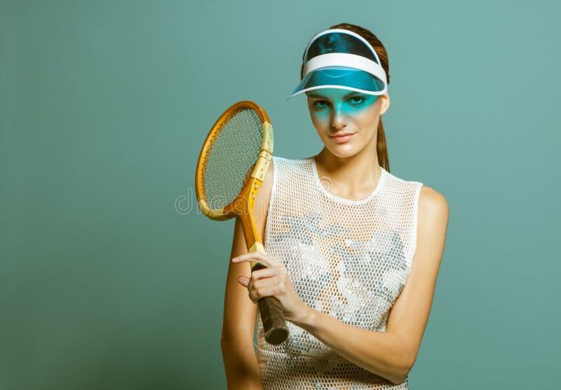 Νέος τενίστας γυναικών στη ρακέτα αντισφαίρισης εκμετάλλευσης γείσων ήλιων στοκ εικόνες