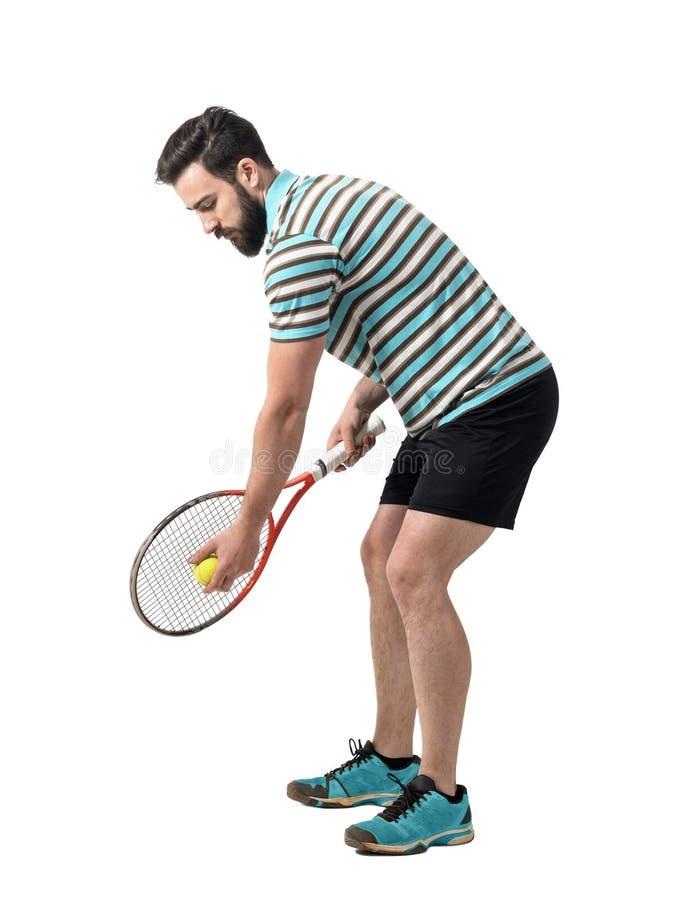 Νέος τενίστας στο πουκάμισο πόλο που προετοιμάζεται να εξυπηρετήσει τη σφαίρα στοκ εικόνες