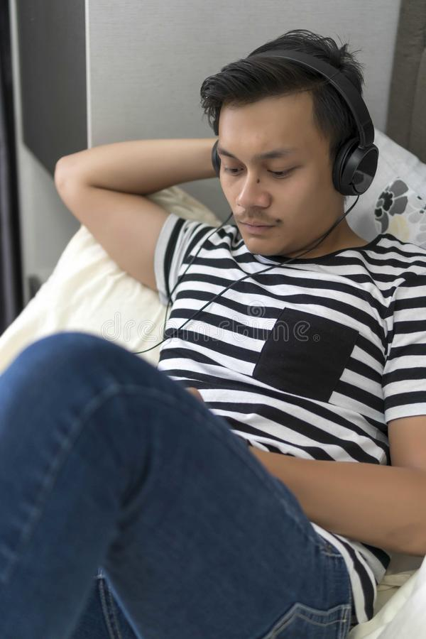 Νέος της Μαλαισίας τύπος που εξετάζει την τηλεφωνική χαλάρωση στοκ εικόνα