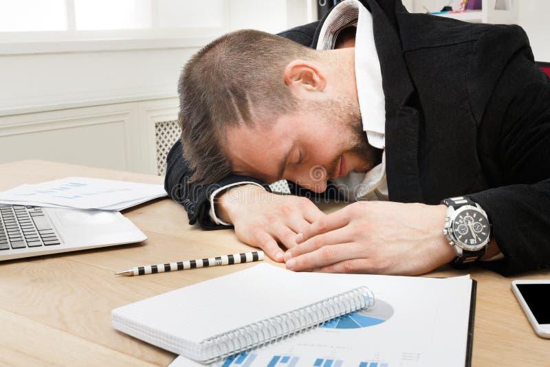 Νέος τονισμένος επιχειρηματίας με το lap-top στο σύγχρονο άσπρο γραφείο στοκ φωτογραφίες με δικαίωμα ελεύθερης χρήσης