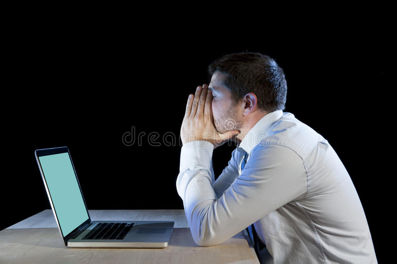 Νέος τονισμένος επιχειρηματίας που εργάζεται στο γραφείο με το lap-top υπολογιστών στην απογοήτευση και την κατάθλιψη στοκ φωτογραφία με δικαίωμα ελεύθερης χρήσης