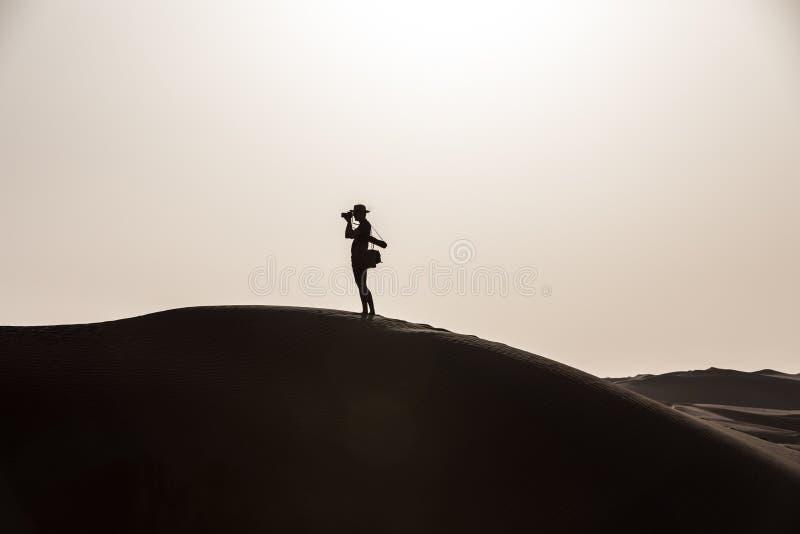 Νέος τουρίστας στα σορτς που στους γιγαντιαίους αμμόλοφους στοκ φωτογραφία με δικαίωμα ελεύθερης χρήσης