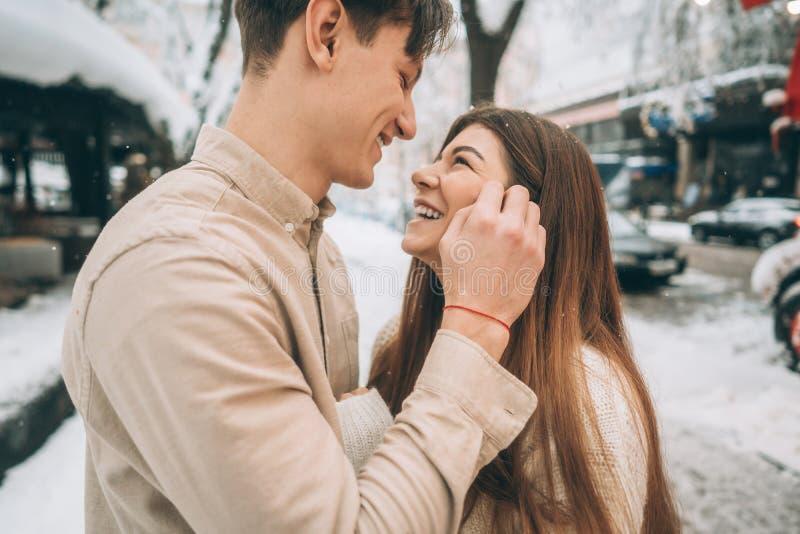 Νέος τύπος και όμορφο φιλί κοριτσιών σε ένα χιονώδες πάρκο Ζεύγος στα πουλόβερ στοκ εικόνες