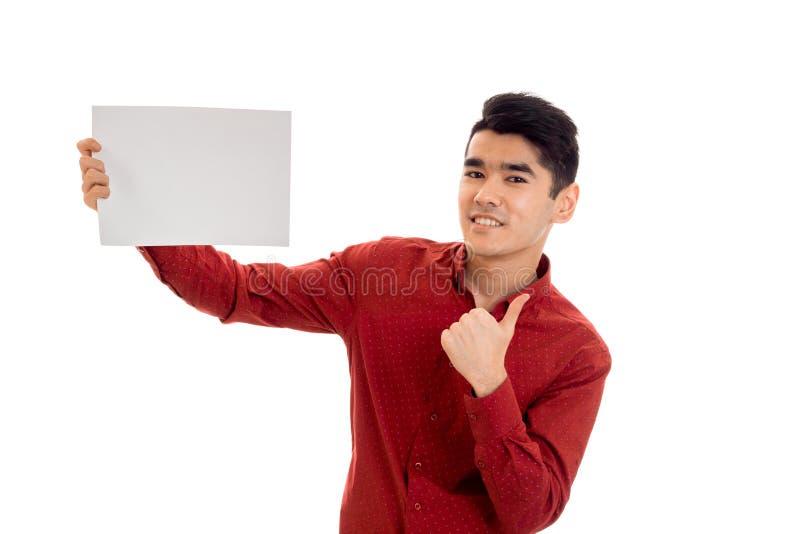 Νέος τύπος κομψότητας στην κόκκινη μπλούζα με την κενή αφίσσα που εξετάζει τη κάμερα και που παρουσιάζει αντίχειρες που απομονώνο στοκ εικόνα