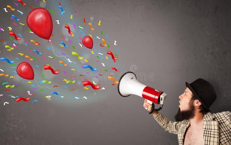 Νέος τύπος που έχει τη διασκέδαση, που φωνάζει megaphone με τα μπαλόνια στοκ φωτογραφίες με δικαίωμα ελεύθερης χρήσης