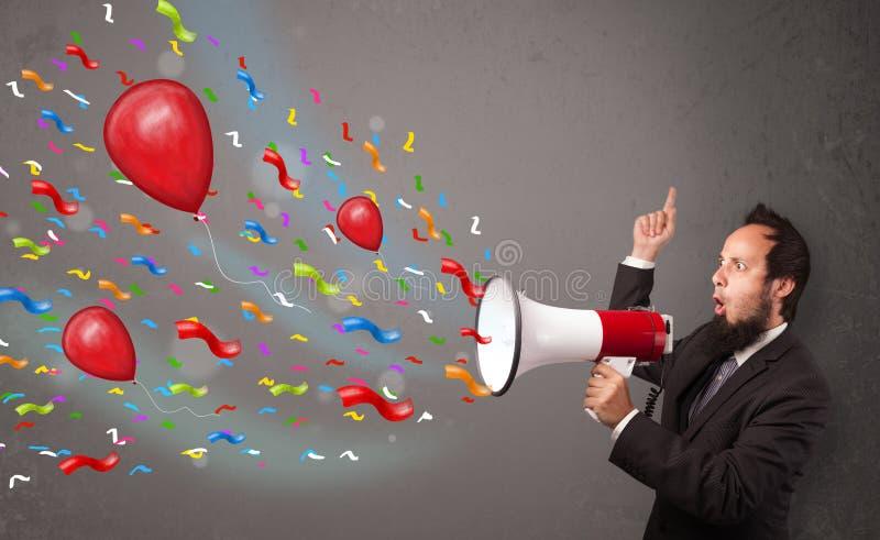 Νέος τύπος που έχει τη διασκέδαση, που φωνάζει megaphone με τα μπαλόνια στοκ εικόνα