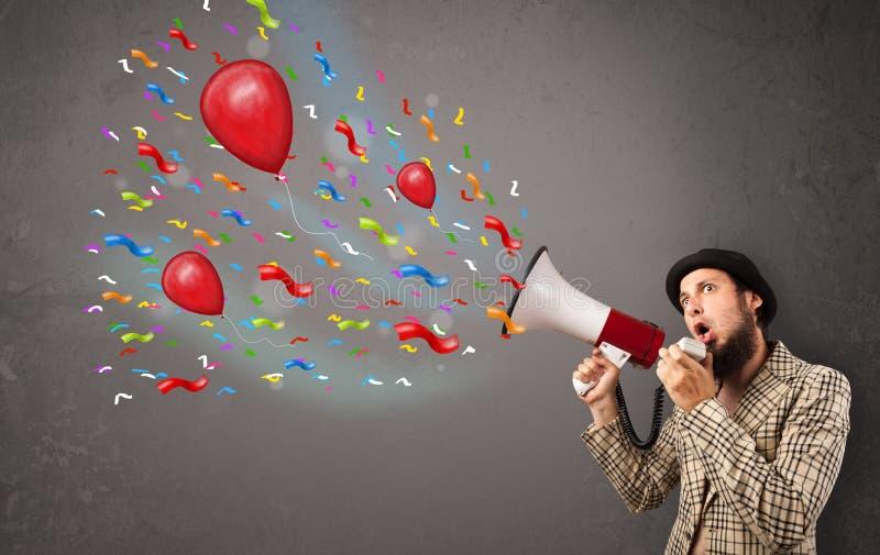Νέος τύπος που έχει τη διασκέδαση, που φωνάζει megaphone με τα μπαλόνια στοκ φωτογραφία