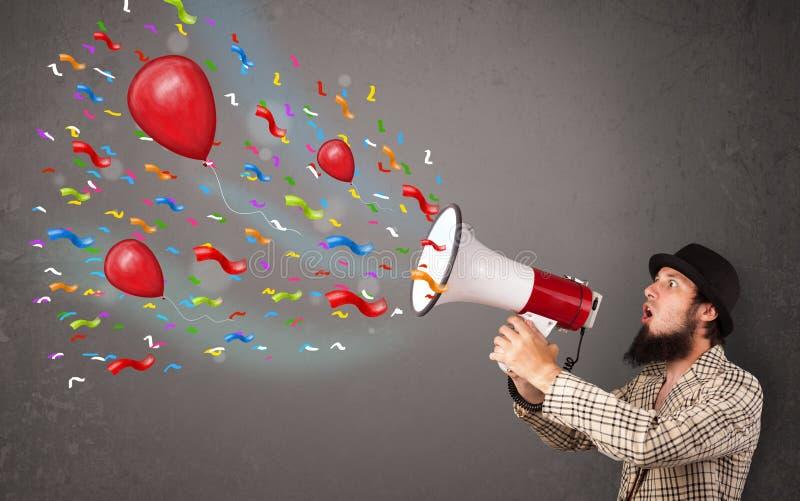 Νέος τύπος που έχει τη διασκέδαση, που φωνάζει megaphone με τα μπαλόνια στοκ φωτογραφία με δικαίωμα ελεύθερης χρήσης