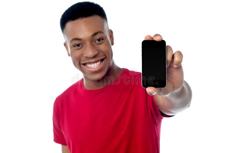 Νέος τύπος που επιδεικνύει το ολοκαίνουργιο κινητό τηλέφωνο στοκ εικόνες