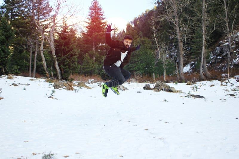 Νέος τύπος που φορά το παλτό και τα γάντια, που πηδά και που απολαμβάνει το χιόνι στοκ φωτογραφίες