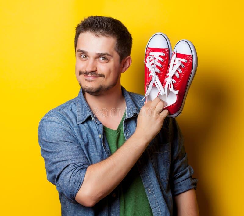 Νέος τύπος χαμόγελου στο πουκάμισο με τα κόκκινα gumshoes στοκ εικόνες