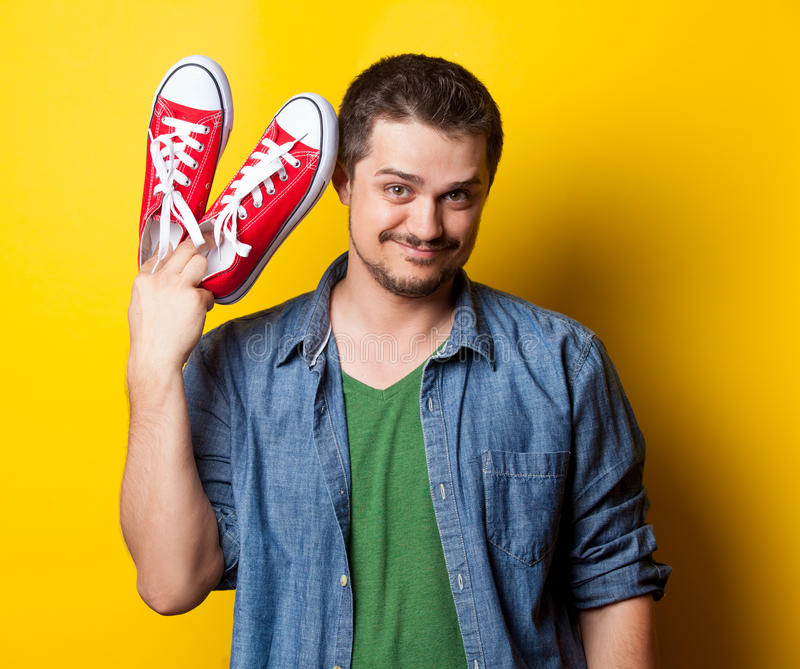 Νέος τύπος χαμόγελου στο πουκάμισο με τα κόκκινα gumshoes στοκ εικόνες με δικαίωμα ελεύθερης χρήσης