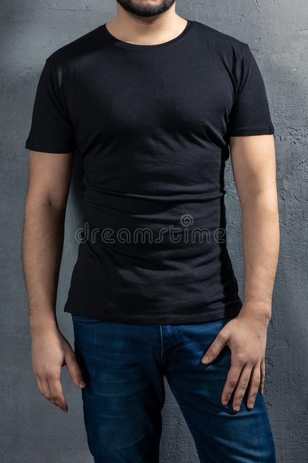Νέος υγιής άνδρας με τη μαύρη μπλούζα στο συγκεκριμένο υπόβαθρο στοκ εικόνα