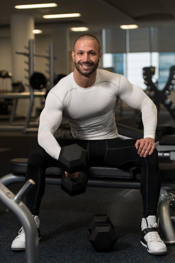 Νέος υγιής άνδρας που κάνει την άσκηση για τους δικέφαλους μυς στοκ φωτογραφία