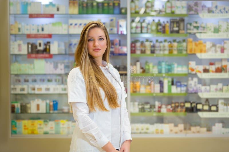 Νέος φαρμακοποιός γυναικών πέρα από το υπόβαθρο φαρμακείων στοκ εικόνα με δικαίωμα ελεύθερης χρήσης