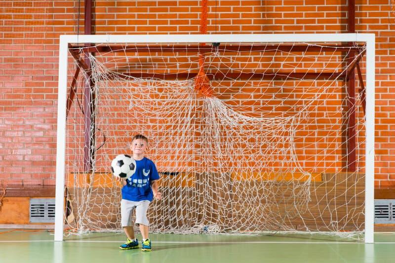 Νέος φύλακας στόχου αγοριών παίζοντας στοκ φωτογραφία με δικαίωμα ελεύθερης χρήσης