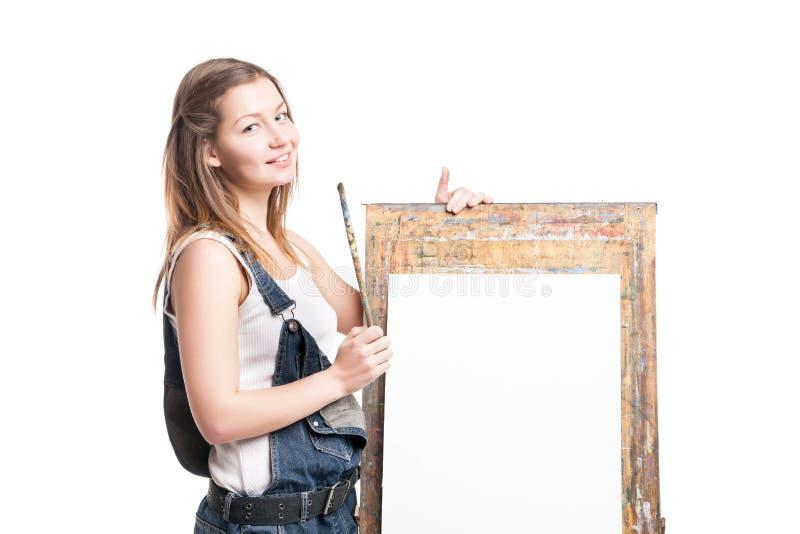 Νέος χαμογελώντας ζωγράφος γυναικών με το πινέλο στοκ εικόνα με δικαίωμα ελεύθερης χρήσης