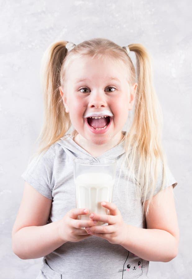 Νέος χαριτωμένος λίγο ξανθό κορίτσι στην άσπρη μπλούζα που χαμογελά και που κρατά το ποτήρι του γάλακτος στοκ φωτογραφίες