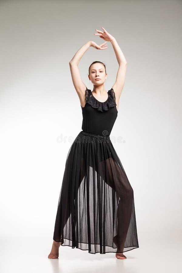 Νέος χορευτής μπαλέτου που φορά το μαύρο διαφανή χορό φορεμάτων στοκ εικόνα