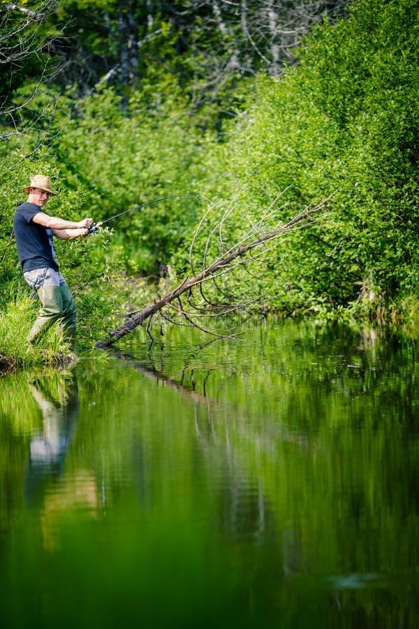 Νέος ψαράς που πιάνει ένα μεγάλο ψάρι στοκ εικόνα με δικαίωμα ελεύθερης χρήσης