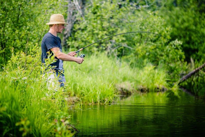Νέος ψαράς που πιάνει ένα μεγάλο ψάρι στοκ φωτογραφία