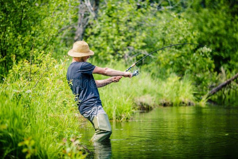 Νέος ψαράς που πιάνει ένα μεγάλο ψάρι στοκ φωτογραφία με δικαίωμα ελεύθερης χρήσης