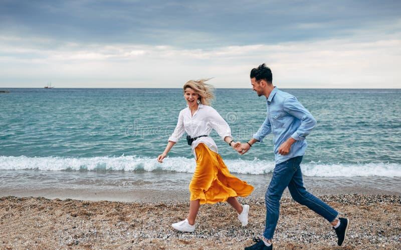 Νέος όμορφος άνδρας και ευτυχής γυναίκα strolling μαζί στην ακτή Το ευτυχές ζεύγος απολαμβάνει μια ημέρα στην παραλία στο μήνα το στοκ εικόνες