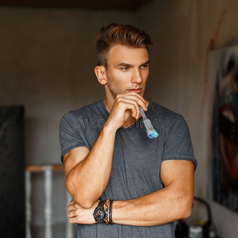 Νέος όμορφος αρσενικός καλλιτέχνης με τη βούρτσα στο δημιουργικό στούντιο στοκ εικόνες