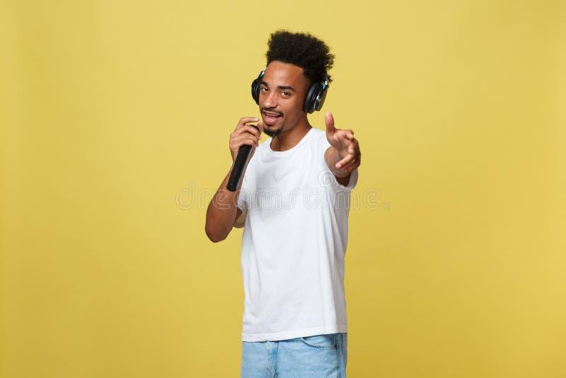 Νέος όμορφος αρσενικός τραγουδιστής αφροαμερικάνων που αποδίδει με το μικρόφωνο Απομονωμένος πέρα από το κίτρινο χρυσό υπόβαθρο στοκ φωτογραφία