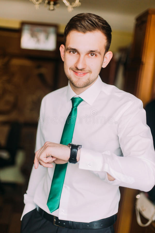 Νέος όμορφος επιχειρηματίας στο άσπρο πουκάμισο με τον πράσινο δεσμό που ελέγχει το χρόνο που κοιτάζει στο ρολόι του στοκ εικόνες με δικαίωμα ελεύθερης χρήσης