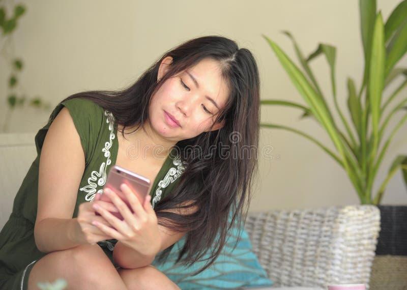 Νέος όμορφος και χαλαρωμένος ασιατικός κινεζικός καναπές καναπέδων καθιστικών γυναικών στο σπίτι που χρησιμοποιεί Διαδίκτυο στο κ στοκ φωτογραφίες