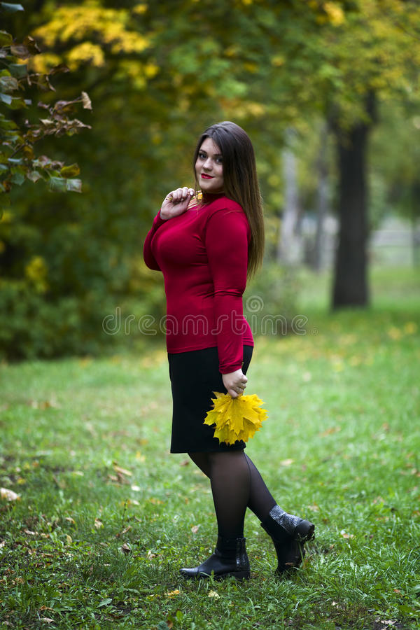 Νέος όμορφος καυκάσιος συν το πρότυπο μεγέθους στο κόκκινο πουλόβερ υπαίθρια, xxl γυναίκα στη φύση, ατμόσφαιρα φθινοπώρου στοκ εικόνες