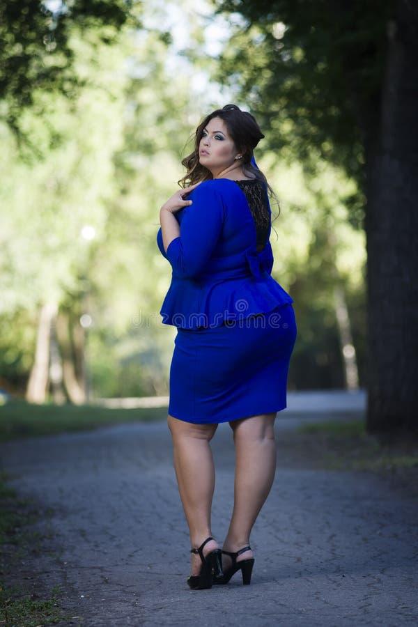 Νέος όμορφος καυκάσιος συν το πρότυπο μόδας μεγέθους στο μπλε φόρεμα υπαίθρια, xxl γυναίκα στη φύση, πίσω άποψη στοκ εικόνα με δικαίωμα ελεύθερης χρήσης