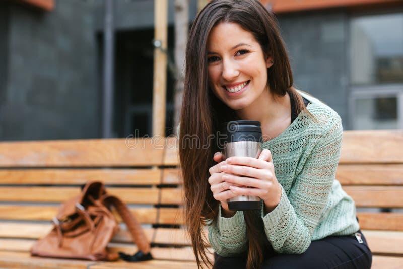 Νέος όμορφος καφές κατανάλωσης γυναικών υπαίθρια στοκ εικόνα με δικαίωμα ελεύθερης χρήσης