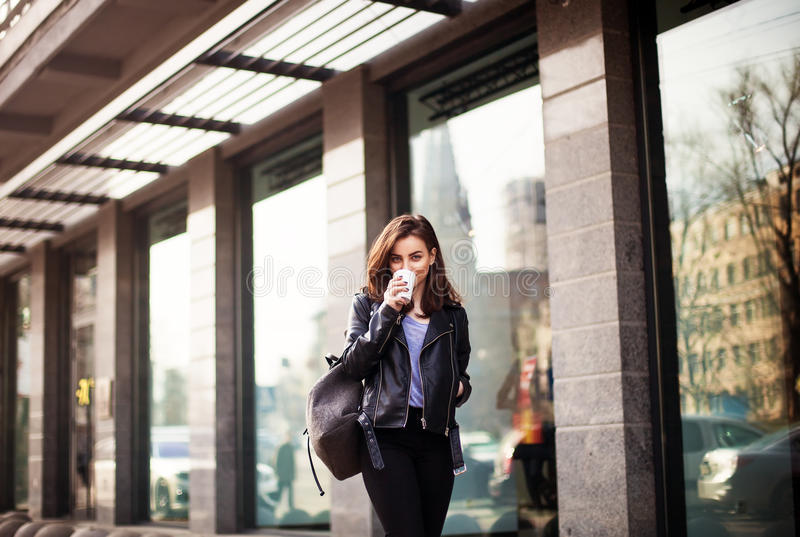 Νέος όμορφος καφές κατανάλωσης brunette που περπατά γύρω από την πόλη σακάκι δέρματος, αστικό σακίδιο πλάτης, φωτεινά κόκκινα χεί στοκ εικόνες