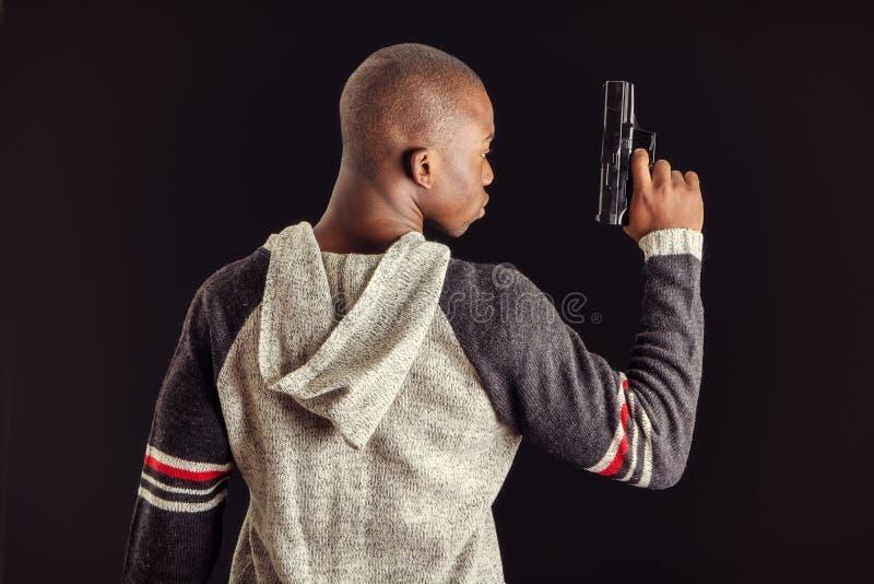 Νέος όμορφος μαύρος που κρατά ένα πυροβόλο όπλο χεριών στοκ εικόνα με δικαίωμα ελεύθερης χρήσης